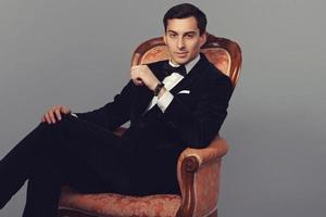Handsome man in suit sitting on vintage armchair. Luxury.