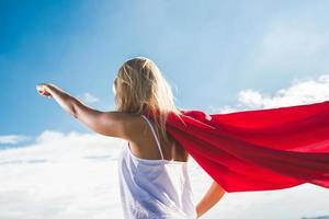 Mujer joven haciéndose pasar por superhéroe sobre el cielo azul foto