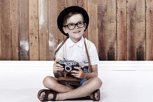 Young boy sitting on floor with camera