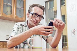 Hombre mensaje de texto en el viejo teléfono móvil en la cocina foto