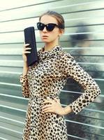 Fashion portrait pretty woman in sunglasses and leopard dress wi photo