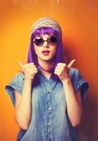 Beautiful girl with violet hair in sunglasses on yellow backgrou photo