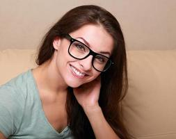 Mujer feliz en vasos en el sofá en casa mirando foto