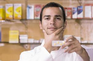 Hispanic pharmacist holding pills up for camera