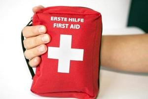 First aid kit with hand - english and german tittle photo