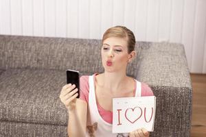 Mujer joven haciendo selfie, te amo en el bloc de notas