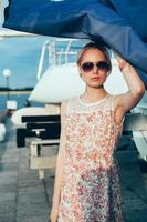 Blonde girl in flower dress and sunglasses holding  boat sails