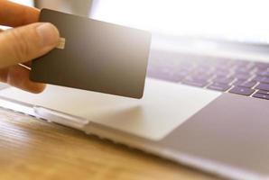 mano que sostiene la tarjeta de crédito cerca de la computadora portátil