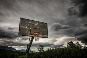 Wooden basketball hoop under dark clouds