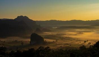 hora dorada sobre montañas y niebla