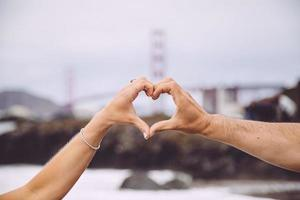 Couple forming heart with hands in front of the Golden Gate Bridge