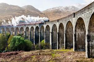Steam train running on concrete bridge