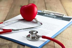 Red stethoscope and heart on clipboard