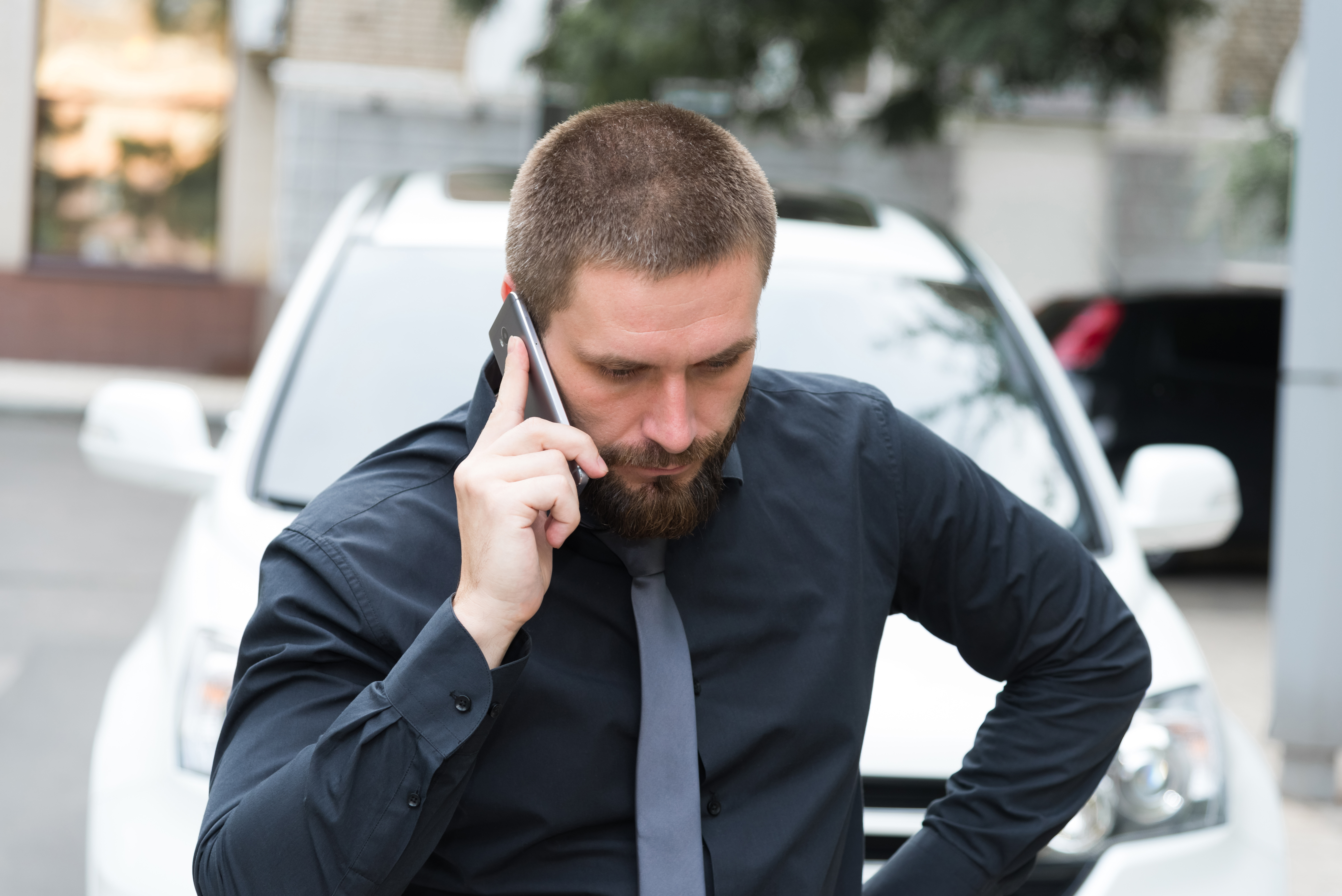 Man talking on phone near a car