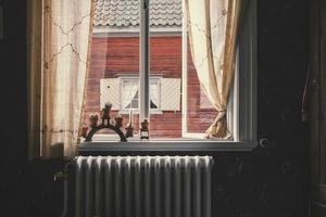 Plants and radiator by open window photo