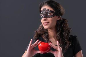 Woman wearing black mask holding heart shape photo