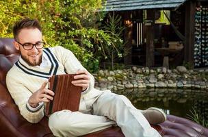 homem bonito sentar no sofá com o ipad no jardim de verão.
