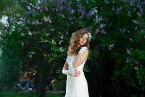 Hermosa novia en vestido blanco sobre fondo lila