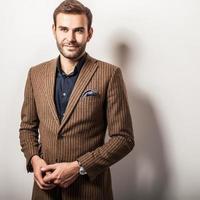 Elegante joven guapo en traje de lujo. Retrato de moda de estudio.