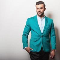 elegante joven apuesto en elegante chaqueta turquesa.