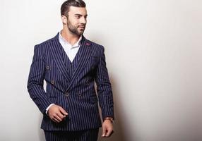 elegante joven apuesto en traje clásico azul oscuro.