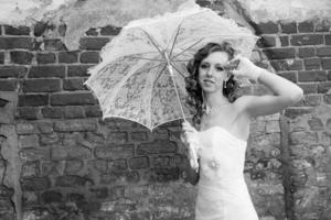 hermosa novia en vestido blanco con paraguas