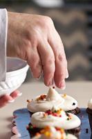 Mano del chef poniendo chispitas en cupcakes foto