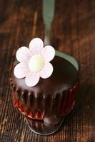 sweet cupcake with chocolate icing on a wooden background
