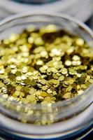 Gold nail glitters close up.