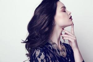mujer sensual con cabello oscuro y maquillaje brillante con bijou