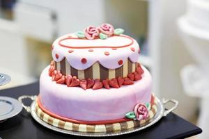 Wedding cake decorated with pink rose flowers and hearts . photo