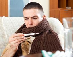 hombre enfermo mirando por termómetro foto