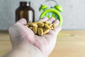 Handful of medicine on wood background photo
