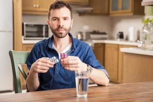Sick looking man taking some medicine photo