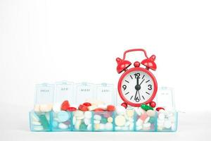 Red alarm clock and medicine in weekly pill box photo