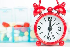 Medicine in weekly pill box and red alarm clock photo