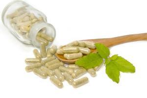 Herbal drug capsules in wooden spoon . Alternative medicine conc