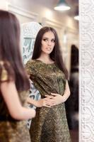 hermosa chica en vestido de brocado dorado mirando en el espejo