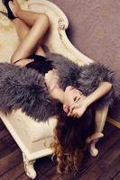 sensual woman with luxurious curly hair wearing elegant fur coat