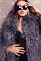 sensual woman with luxurious curly hair wearing elegant fur coat