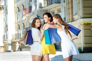 Hugging girlfriends. Three attractive young girls holding  bags