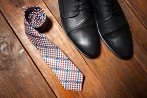leather footwear and a checkered tie