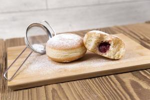 Fresh donuts on wooden table photo