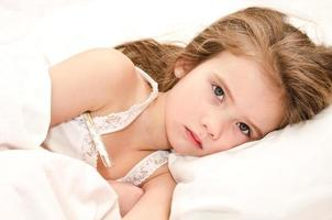niña enferma acostada en la cama foto