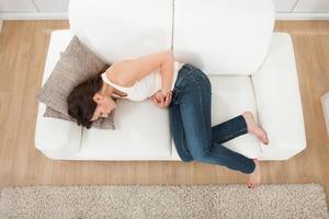 Imagen de arriba hacia abajo de la mujer dolorida sujetando la barriga acurrucada en el sofá