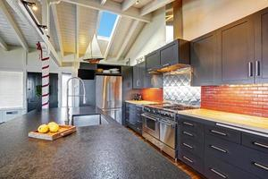 Luxury beautiful dark modern kitchen with vaulted wood ceiling.