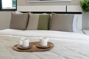 Decorative wooden tray with tea set on bed photo
