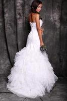 Hermosa joven novia con cabello oscuro en vestido de novia