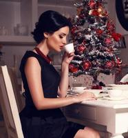 linda mulher com cabelo escuro tomando café
