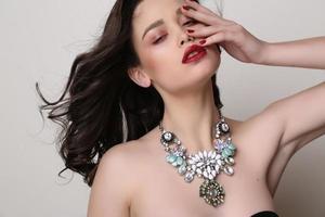 mujer con cabello oscuro y maquillaje brillante, con lujoso collar